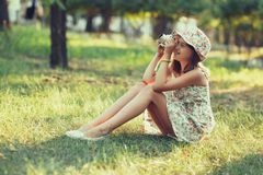 Little girl is played by photo camera sitting on grass in park. Doing Selfie and photographing the world around Royalty Free Stock Photo