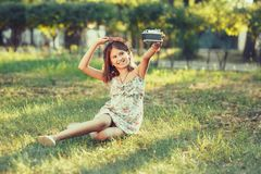 Little girl is played by photo camera sitting on grass in park. Doing Selfie and photographing the world around Stock Images