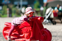 Little girl at playground. Sitting on a motorcycle Royalty Free Stock Photo