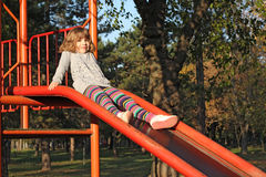 Little girl on playground. Slide Stock Images