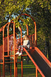 Little girl on playground. Slide Stock Image