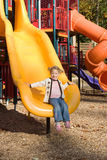 Little girl at playground. Happy little girl on slide at elaborate outdoor playground Stock Photos