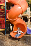 Little girl at playground. Happy little girl on slide at elaborate outdoor playground Stock Image