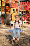 Little girl at playground. Happy little girl on swing at elaborate outdoor playground Stock Photo