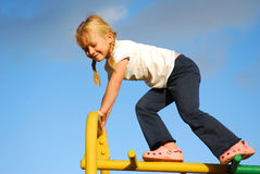 Little girl on playground. Cute little caucasian girl child climbing on a jungle gym at the playground outdoors Stock Photo