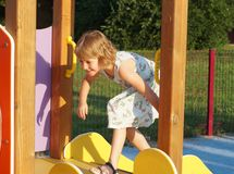 A little girl on a playground. Child activities on a children playground. A little girl on a playground. Child development activities on a children playground stock photos