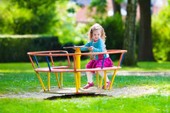 Little girl on a playground. Child playing outdoors in summer. Kids play on school yard. Happy kid in kindergarten or preschool. Children having fun at daycare Royalty Free Stock Image