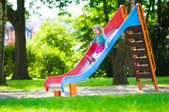 Little girl on a playground. Child playing outdoors in summer. Kids play on school yard. Happy kid in kindergarten or preschool. Children having fun at daycare Stock Photography
