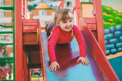 Little girl on the playground. Little girl on the playground descending on a slide Stock Image