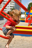 Little girl on playground equipment Stock Image