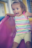 Little girl in playground. Happy little girl descends from the slide Stock Photography