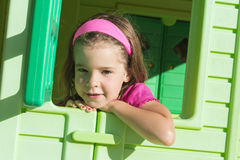 Little girl in playground house Royalty Free Stock Image