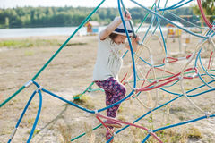 Little girl on the playground with rope ladder. Playground outdoors on the beach near the lake Stock Photos