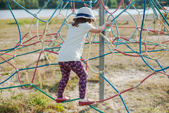 Little girl on the playground with rope ladder. Playground outdoors on the beach near the lake Stock Image