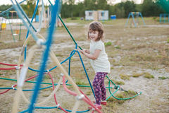Little girl on the playground with rope ladder. Playground outdoors on the beach near the lake Stock Photography
