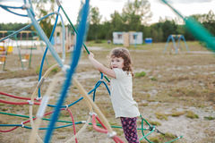Little girl on the playground with rope ladder. Playground outdoors on the beach near the lake Stock Photo