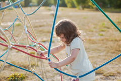 Little girl on the playground with rope ladder. Playground outdoors on the beach near the lake Royalty Free Stock Images