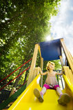Little girl on playground slide. Little girl with yellow hat playing on yellow playground slide Stock Photography