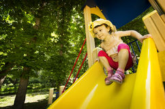 Little girl on playground slide. Little girl with yellow hat playing on yellow playground slide Royalty Free Stock Images