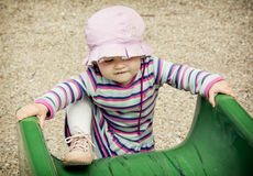 Little girl and playground slide Stock Photo
