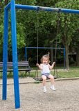 Little girl at playground swinging Royalty Free Stock Photos