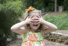 Little girl playing. Cute girl playing with hands over eyes Royalty Free Stock Photos