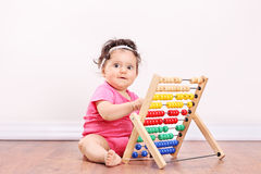 Little girl playing with an abacus seated on floor Royalty Free Stock Photography
