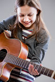 Little girl playing acoustic guitar Royalty Free Stock Images