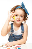 Little girl playing in the alphabet. Shows the letter Т. Royalty Free Stock Photography