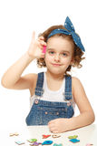 Little girl playing in the alphabet. Shows the letter I. Royalty Free Stock Photo