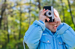 Little girl playing at amateur photography. Holding an old retro slr camera to her eye while standing in a wooded park royalty free stock photography