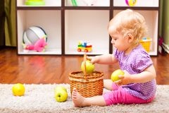 Little girl playing with apple and lemons Stock Image