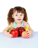 Little girl playing with apples sitting at table Stock Photos