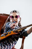 Little girl playing as a guitar hero rockstar Stock Image