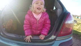 Little girl playing in automobile trunk video stock video