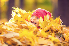 Little girl playing with autumn leaves Stock Images