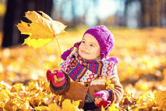 Little girl playing with autumn leaves Royalty Free Stock Photos