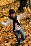 Little girl playing in autumn park Stock Photos