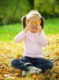 Little girl is playing in autumn park Royalty Free Stock Image