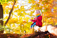 Little girl playing in autumn park Stock Photo