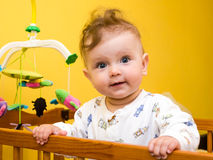 Little girl playing in the baby crib Stock Images