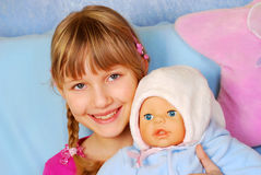 Little girl playing with baby doll Stock Image