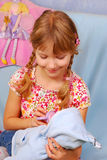 Little girl playing with baby doll Royalty Free Stock Images