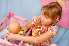 Little girl playing with  baby doll Royalty Free Stock Photo