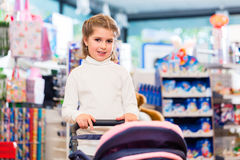 Little girl playing with baby doll carriage in toy store Stock Photography
