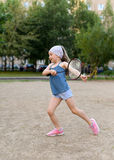 A little girl playing badminton in a yard of an apartment buiding Stock Images
