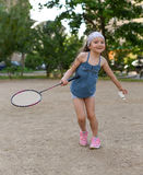 A little girl playing badminton in a yard of an apartment buiding Royalty Free Stock Photography