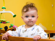 Little girl playing ball in the baby crib Stock Photos