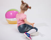 Little girl playing with a ball. On the floor Royalty Free Stock Images