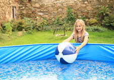 Little girl playing with ball in pool Stock Image